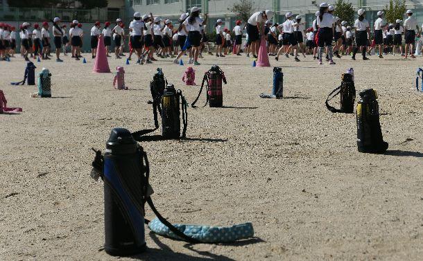 写真・図版 : 運動会の練習風景。運動場に置かれた水筒からも児童らが「ソーシャルディスタンス」を意識していることがうかがえる=2020年9月28日、名古屋市瑞穂区