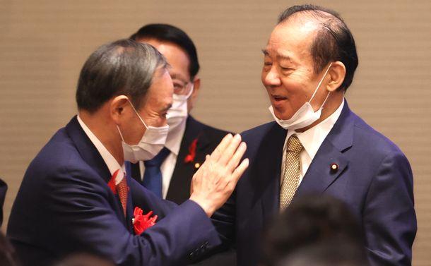 写真・図版 : 自民党の二階俊博幹事長(右)の派閥による政治資金パーティーに、来賓として出席した菅義偉首相=2020年10月7日、東京都千代田区