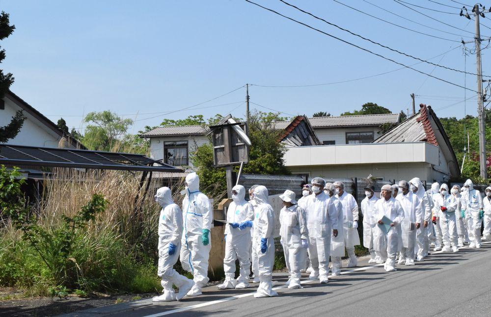 写真・図版 : 福島県富岡町の帰還困難区域を視察する仙台高裁の裁判官ら=2019年5月