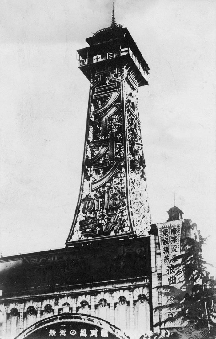 写真・図版 : 1935年(昭和10)頃の初代通天閣。右下に浪曲の黄金期を支えた東家楽燕と二代目広沢虎造の公演を知らせる垂れ幕が見える