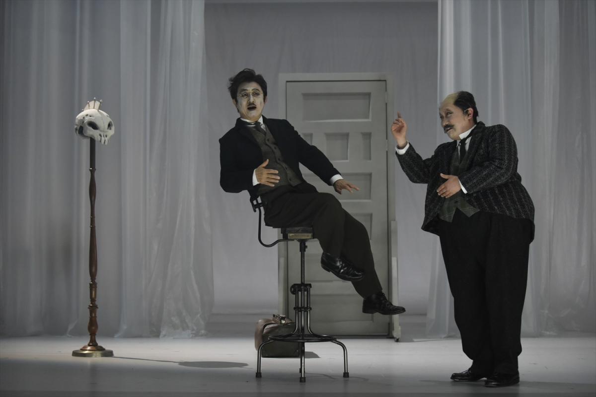 写真・図版 : まつもと市民芸術館で上演された『白い病』(公演のタイトルは『白い病気』)の舞台。医師ガレーン役の串田和美(演出も、左)と、ジーゲリウス役の武居卓=2018年、山田穀撮影