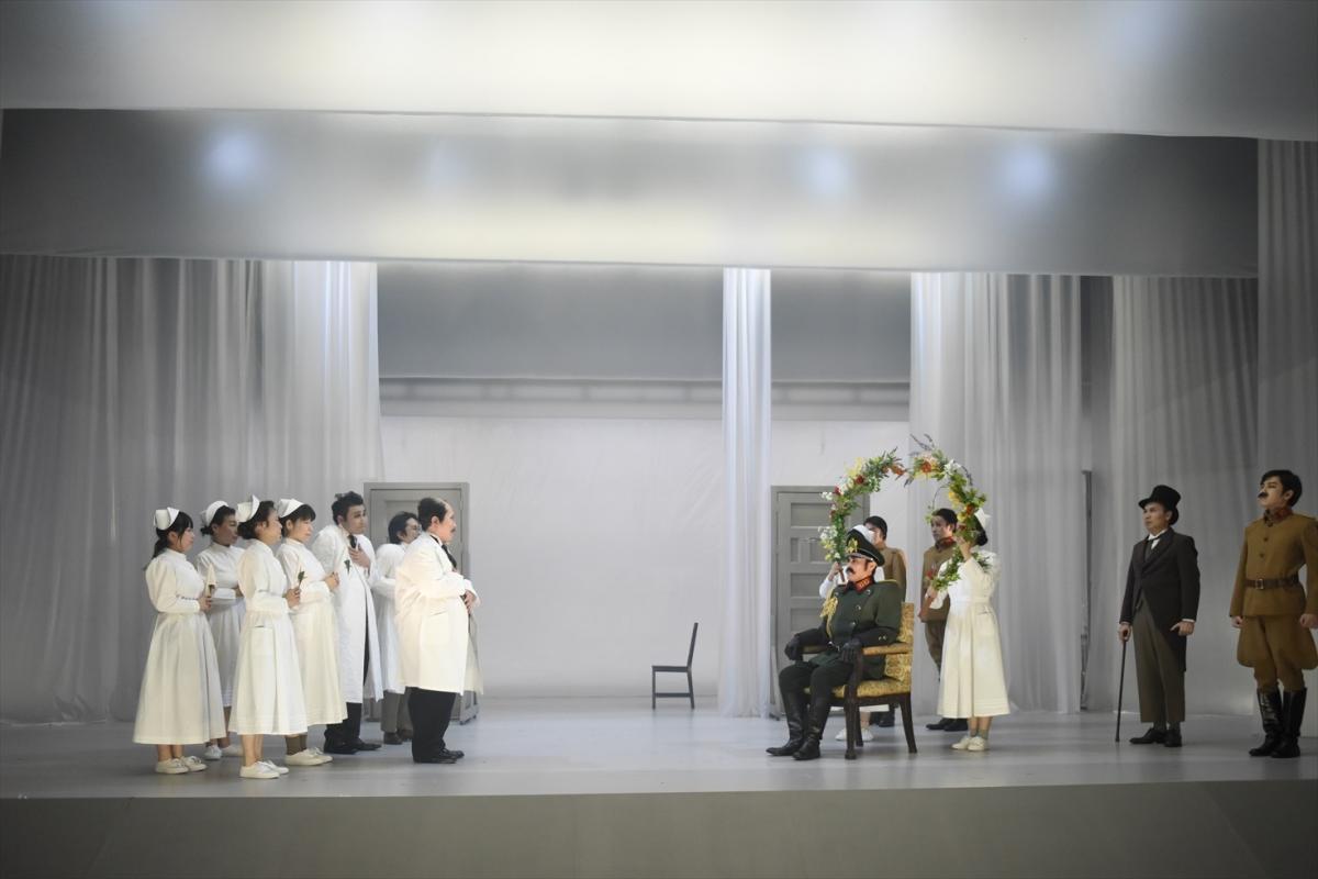 写真・図版 : まつもと市民芸術館で上演された『白い病』(公演のタイトルは『白い病気』)の舞台。中央が元帥役の横田栄司=2018年、山田穀撮影