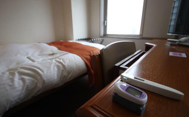 写真・図版 : 療養用に自治体(大分県)が借り上げたホテルの部屋。体温計と血中酸素濃度計(手前)が用意されていた=2020年8月7日、大分市