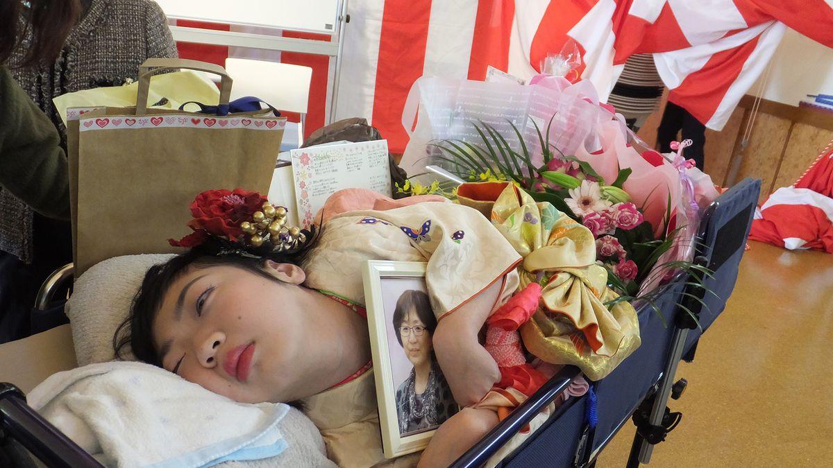写真・図版 : 母の遺影を抱いて成人式を迎える沖茉里子さん