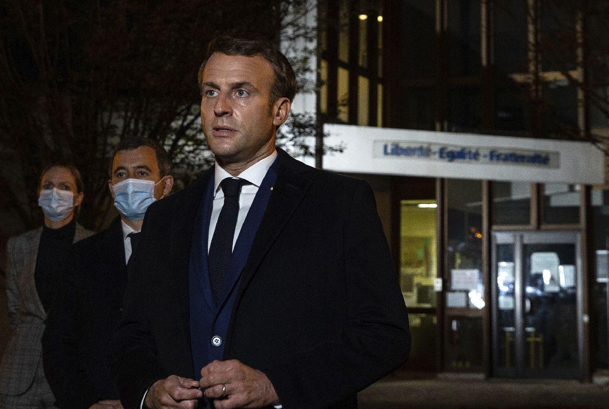写真・図版 : パリ北西部コンフランサントノリヌで16日夜、殺害された教員が勤務していた中学校前で報道陣に語るマクロン大統領=2020年10月16日、AP