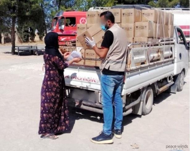 写真・図版 : 国際協力NGO「ピースウィンズ・ジャパン」の現地スタッフがシリア国内で支援物資を配る様子(一部にモザイク処理)=2020年8月、ピースウィンズ・ジャパン提供
