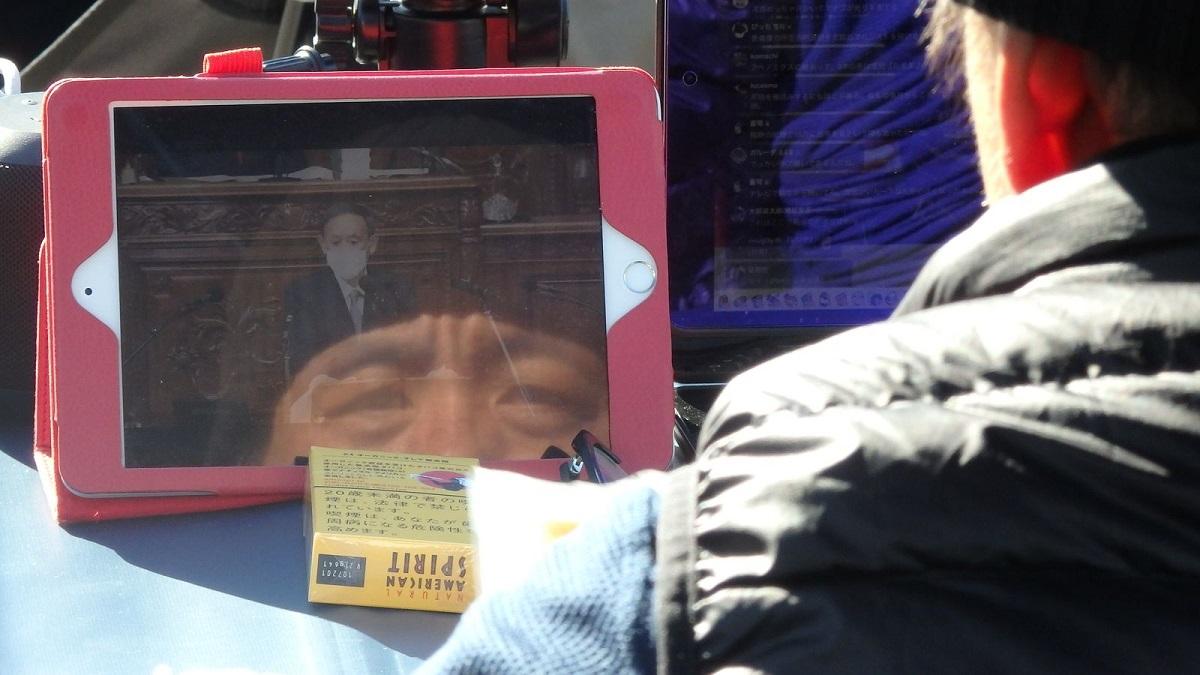 写真・図版 : 菅義偉首相の所信表明演説をテレビで見る菅野氏(ハンスト最終日)=10月26日、首相官邸前