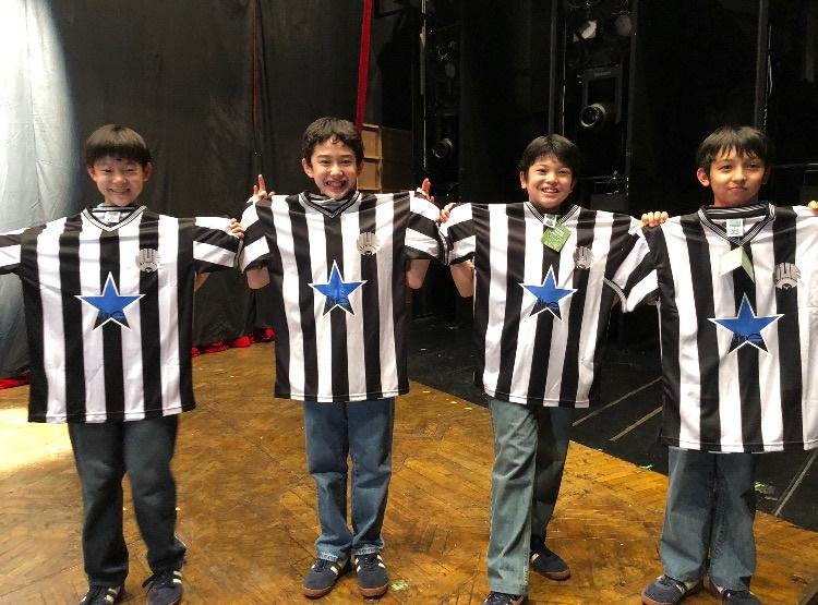 写真・図版 : 初⽇のお祝いに演出補のサイモンから主役の4⼈に、ビリーが好きなサッカーチームのユニホームが贈られた