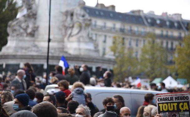 写真・図版 : パリのレピュブリック広場で10月18日、教員サミュエル・パティ氏の殺害事件の追悼に集まった市民。表現の自由を訴えようと、風刺週刊紙「シャルリー・エブド」(右下)も掲げられた=2020年10月18日、疋田多揚撮影