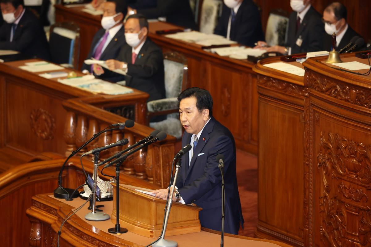写真・図版 : 衆院本会議で代表質問に立つ、立憲民主党の枝野幸男代表(手前)。後方左は菅義偉首相=2020年10月28日