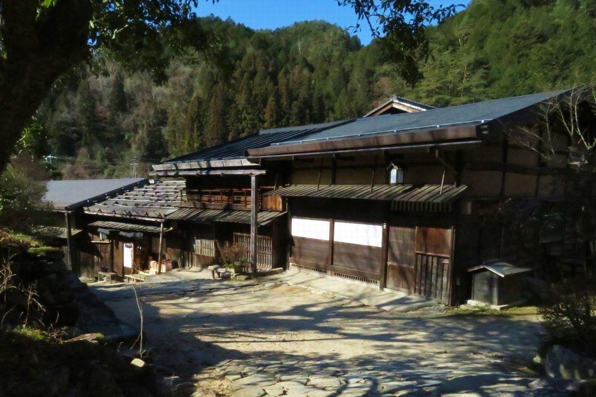 写真・図版 : 枡形跡の近くには石置き屋根なども見られる。背後の山並みと一体に、往時の宿場の風情を醸し出している=筆者撮影