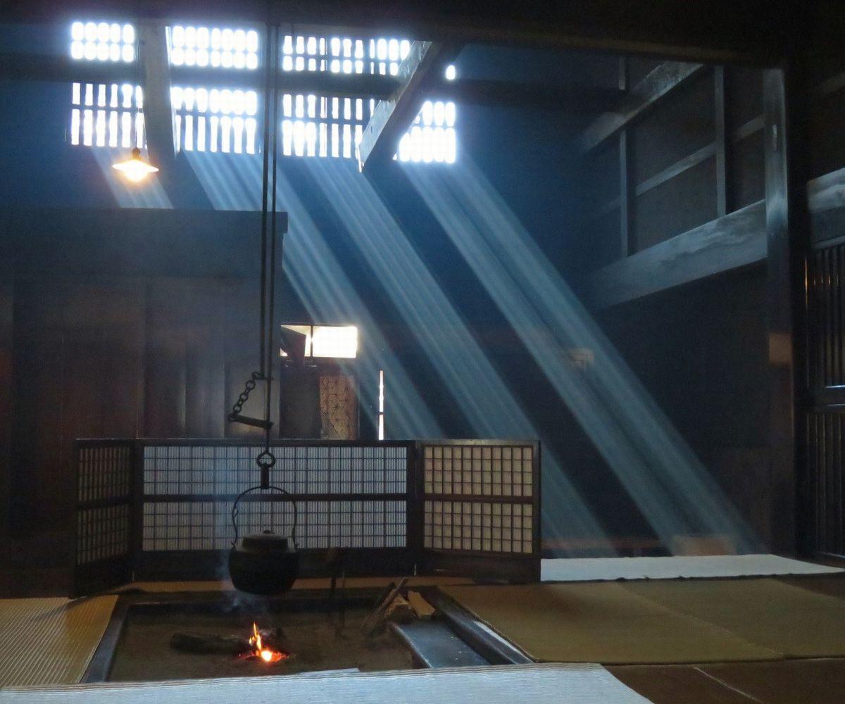 写真・図版 : 妻籠宿の街道筋に立つ国の重要文化財「脇本陣奥谷」の内部。囲炉裏の煙に、格子窓から差し込んだ陽が舞台照明のように浮かぶ=2019年、筆者撮影