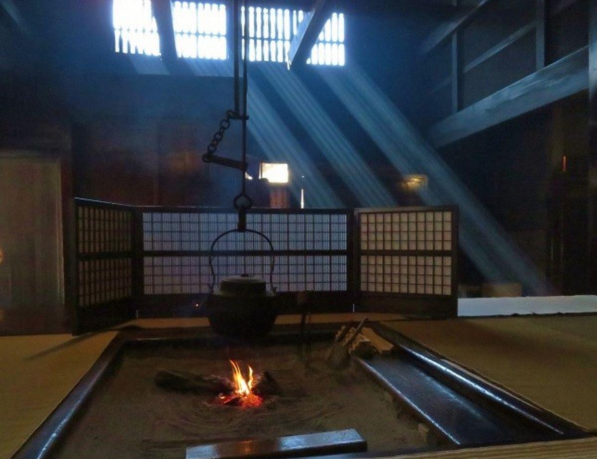 写真・図版 : 脇本陣奥谷の居間。囲炉裏から上がる煙に格子窓から光線が差し込み、美しい空間を作り出す=2019年、筆者撮影