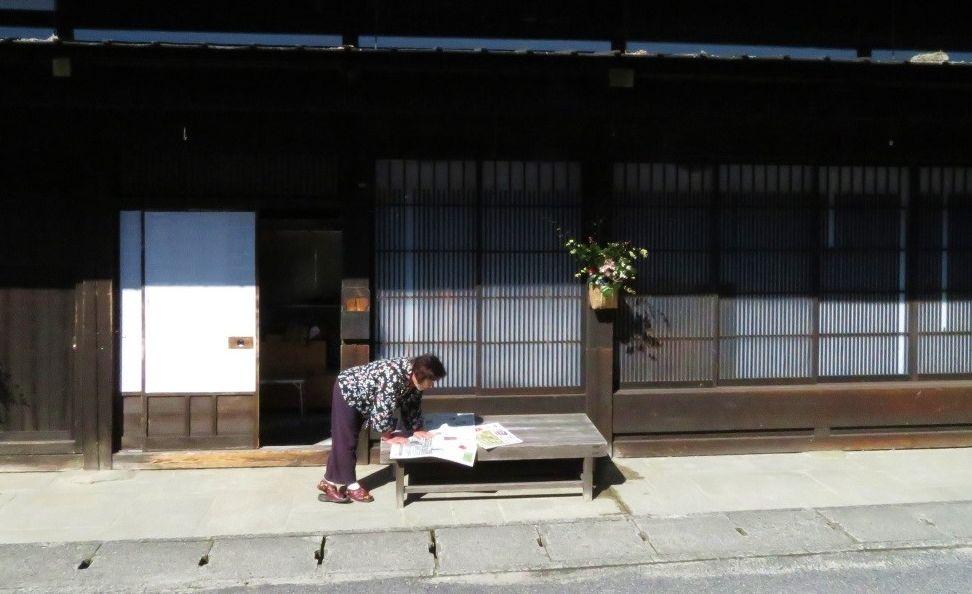 写真・図版 : 今昔が溶け合う妻籠宿の暮らし。竹かごに活けられた花が旅人を迎えてくれるよう=筆者撮影