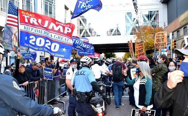 写真・図版 : 大統領選の開票作業が続く米ペンシルベニア州フィラデルフィアで、警官隊を挟んでにらみ合うトランプ大統領の支持者(左)と、バイデン氏の支持者ら=2020年11月6日