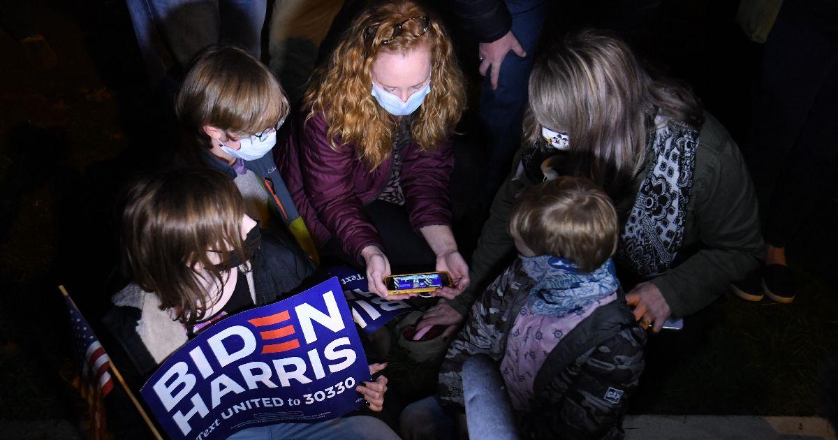 写真・図版 : バイデン氏の演説会場の近くで、スマートフォンを使って中継動画を見る家族=2020年11月6日午後10時54分、米デラウェア州ウィルミントン、藤原学思撮影