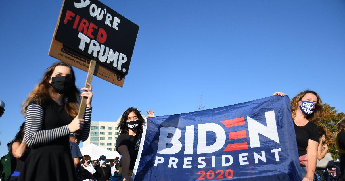 写真・図版 : バイデン氏の演説会場を訪れた支持者たち。トランプ大統領がかつて司会を務めていた番組の決めぜりふ「君はクビだ!」と書いたプラカードを持つ女性の姿もあった=2020年11月7日、デラウェア州ウィルミントン、藤原学思撮影