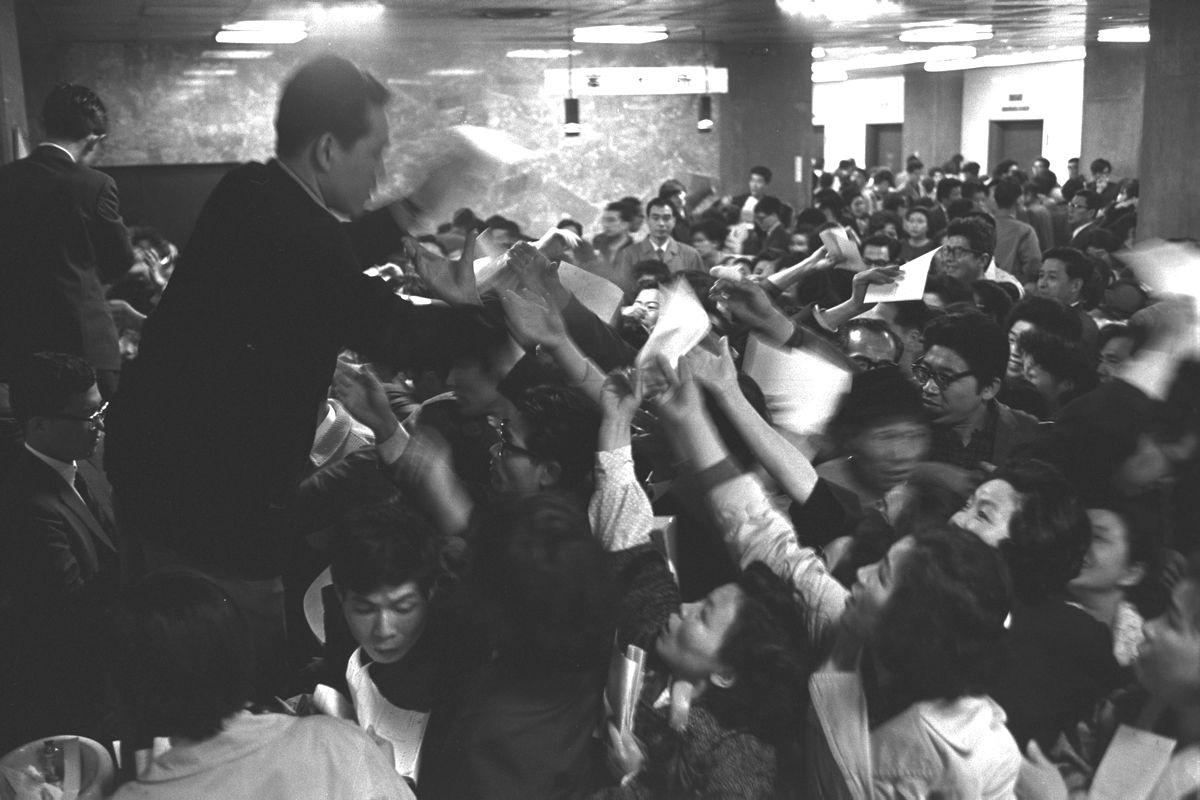 写真・図版 : 都営住宅の空き家募集の受け付けを始めると、初日の午前中だけで2万人が殺到し、パトカーが出動する騒ぎに。写真は大混雑する東京都庁第2庁舎=1966年4月4日、東京都千代田区丸の内