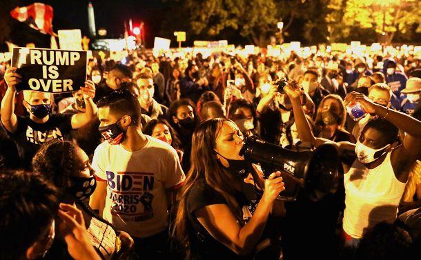 写真・図版 : ホワイトハウス近くで日没後、バイデン氏が当選確実となったことを祝い、「トランプ氏は終わりだ」と叫ぶ人たち=2020年11月7日、ワシントン