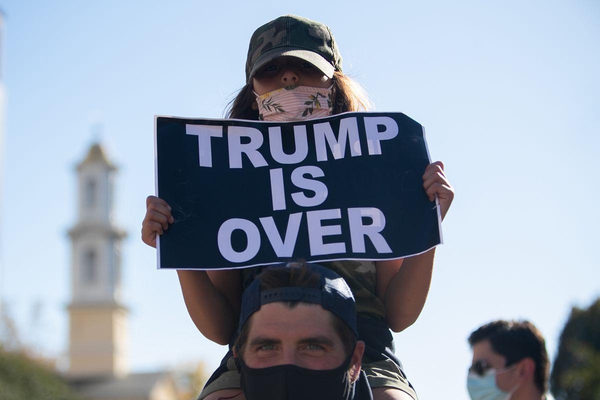 11月7日、ホワイトハウス周辺で「トランプは終わった」というプラカードを掲げてバイデン氏の勝利を祝う親子=ワシントン、ランハム裕子撮影