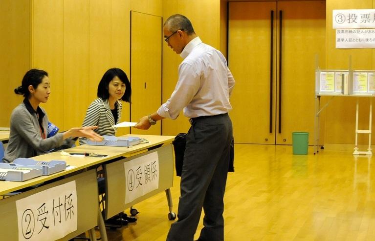 写真・図版 : 2013年の衆院選のとき北京の日本大使館で投票する日本人有権者(右)。投票箱はなく、記入した投票用紙を封筒に入れて職員に渡す。投票用紙入りの封筒は郵送ではなく職員が外務省へ運ぶ=2013年7月15日、中国・北京、今村優莉撮影
