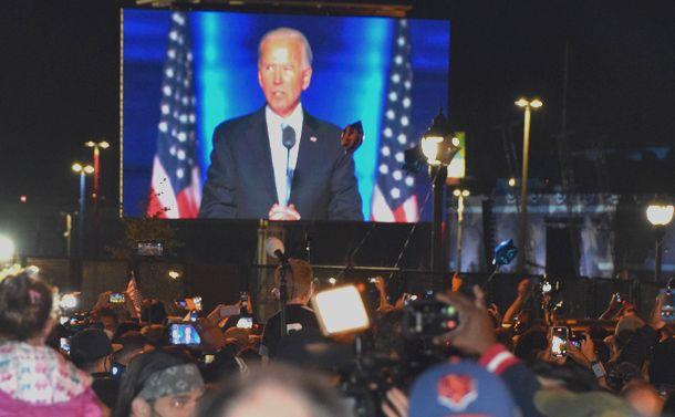 写真・図版 : バイデン氏の勝利宣言を演説会場の外で見守り、歓声をあげる支持者ら=2020年11月7日、米デラウェア州ウィルミントン