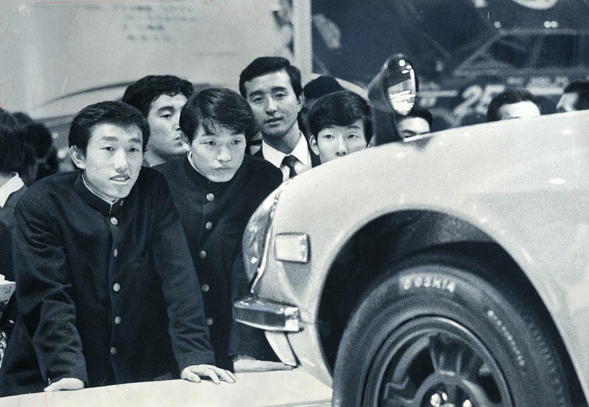 写真・図版 : 晴海のモーターショーで新車に目を輝かす高校生たち=1969年10月、東京都中央区