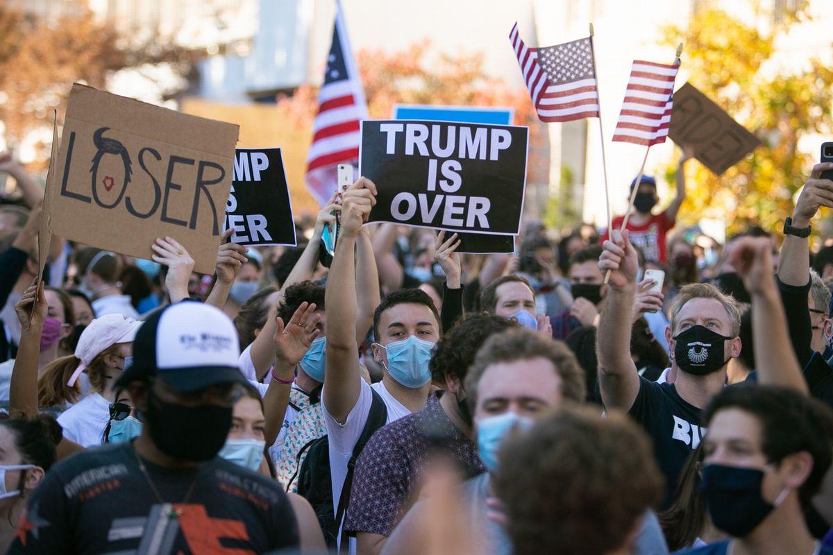 ホワイトハウス周辺で「トランプは終わった」などと書かれたプラカードを掲げ、バイデン氏の勝利を祝う人たち=2020年11月7日、ワシントン、ランハム裕子撮影