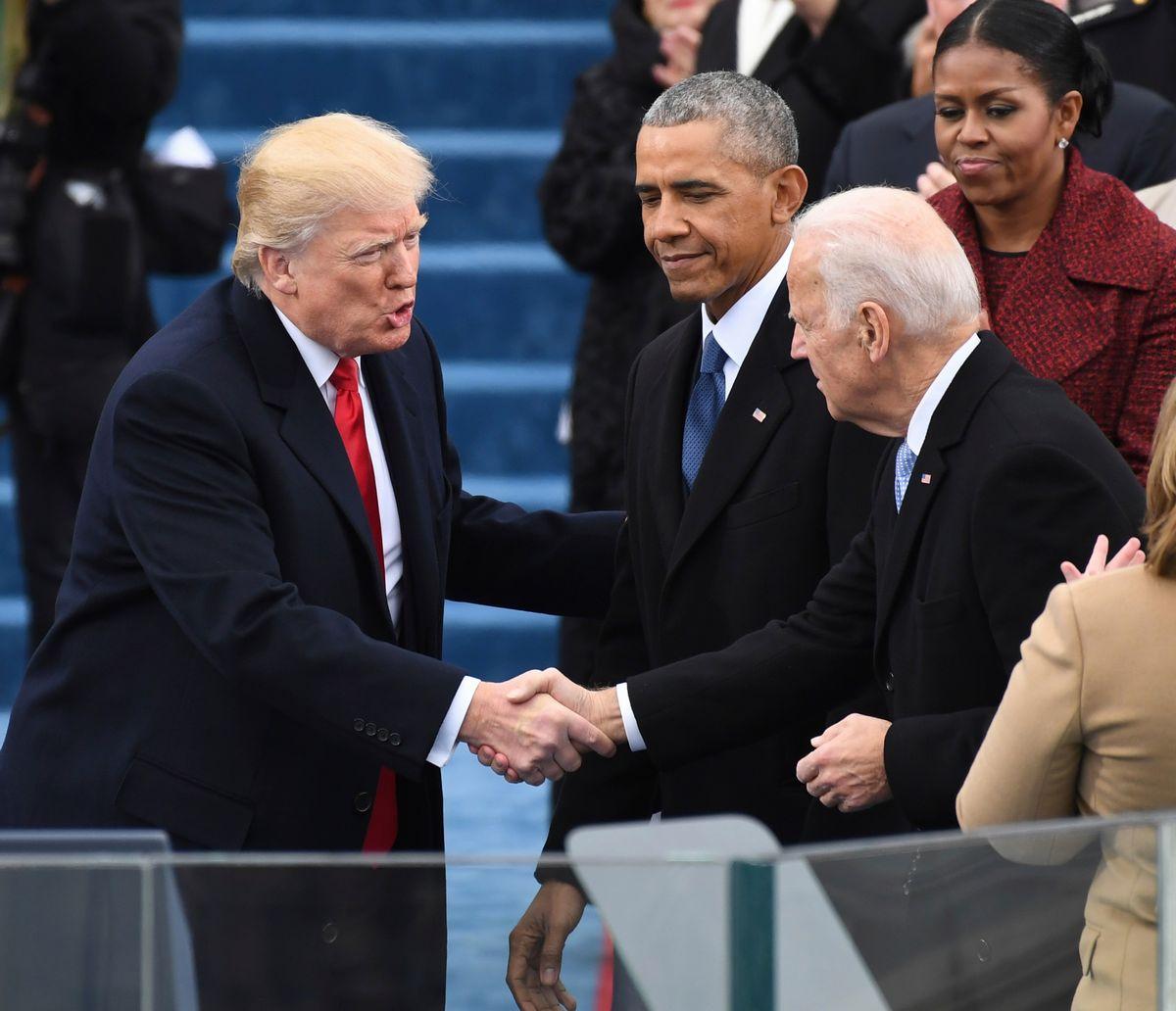 写真・図版 : トランプ大統領の就任式に到着したバイデン氏と握手を交わすトランプ氏。中央はオバマ氏=2017年1月20日、ワシントン、Alex Gakos / Shutterstock.com