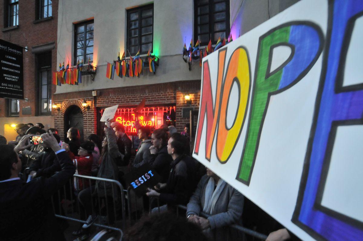 写真・図版 : トランスジェンダーの生徒らを保護するオバマ前政権時代の通達を撤回したトランプ政権に抗議する人たち。奥に見えるのが、バー「ストーンウォール・イン」=2017年2月23日、米ニューヨークのグリニッチビレッジ