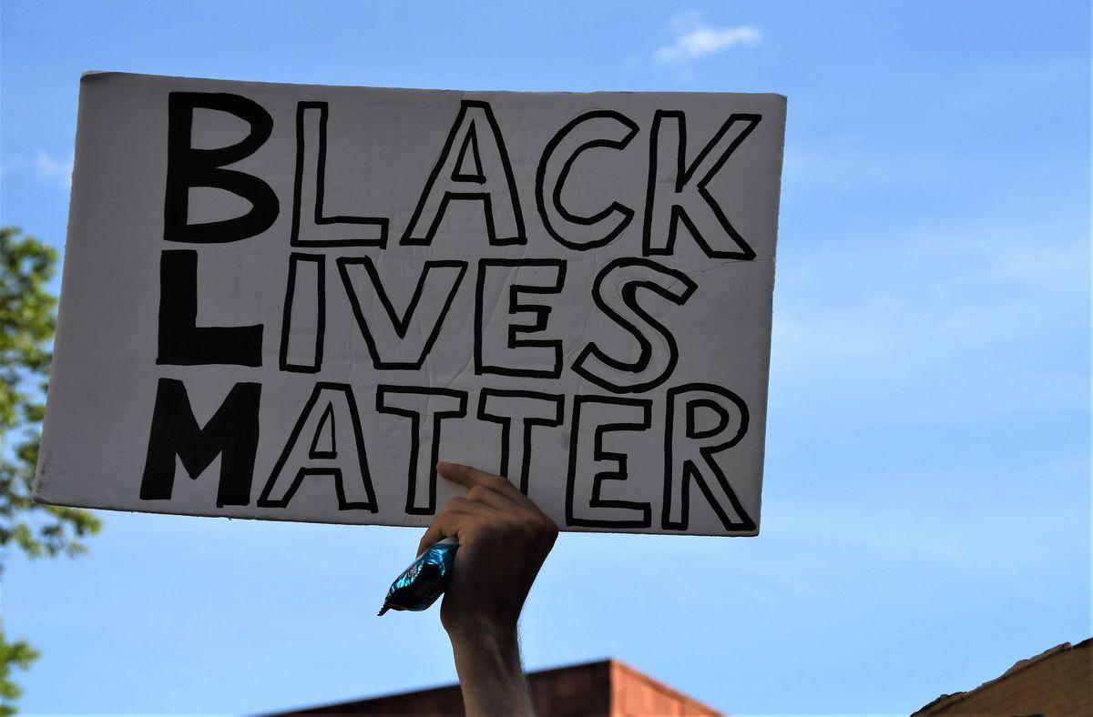 写真・図版 : ジョージ・フロイドさんの事件に端を発する抗議デモで掲げられたBLACK LIVES MATTERのプラカード=2020年6月8日、ニューヨーク