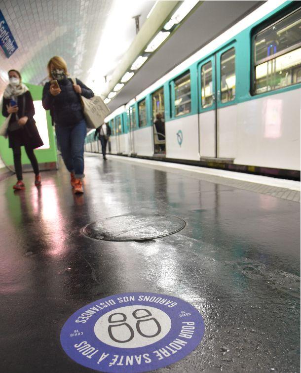 写真・図版 : マスクを着用したパリの地下鉄の利用客。ホームには「距離をとろう。私たちみんなの健康のために」と記されたマーク(手前)が=2020年5月11日、疋田多揚撮影