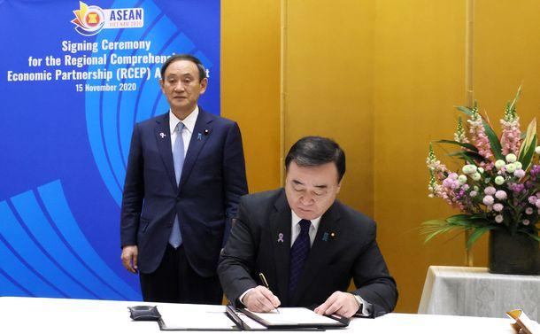 写真・図版 : RCEPに署名する梶山弘志経済産業相(右)と、同席する菅義偉首相(左)=2020年11月15日、官邸、内閣広報室提供