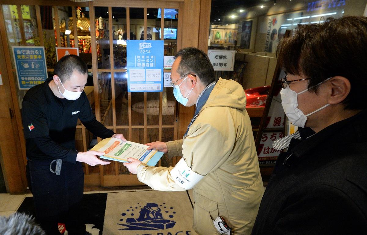 居酒屋の店長に深夜営業の自粛などをお願いする道と札幌市の職員=札幌市中央区20201114