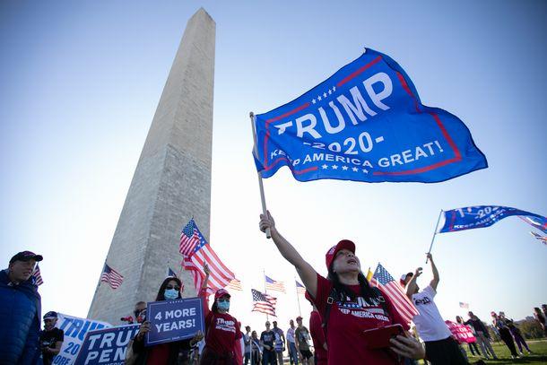 写真・図版 : ワシントン記念塔に集まり、「あと4年」などと叫ぶトランプ氏の支持者たち=2020年11月7日、ワシントン