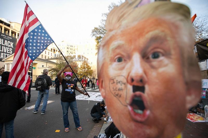 写真・図版 : ホワイトハウス周辺でトランプ大統領に対する抗議運動をする女性=2020年11月5日、ワシントン