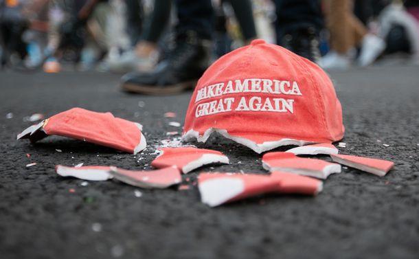 写真・図版 : 「米国を再び偉大に」というトランプ大統領のスローガンが書かれた陶器の帽子がホワイトハウス前で割られていた=2020年11月3日、ワシントン