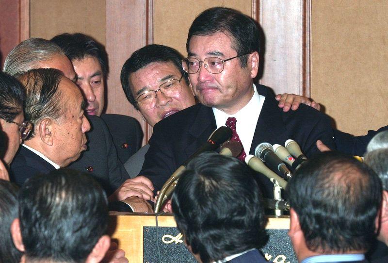 写真・図版 : 内閣不信任案に賛成票を投じると発言した加藤元幹事長は、合同総会に出席した議員から押しとどめられ、涙を浮かべた=2000年11月20日、東京都港区