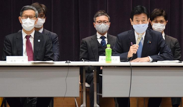 写真・図版 : 11月25日に開かれた新型コロナウイルス感染症対策分科会であいさつする西村康稔経済再生相(右)。並んで座るのは尾身茂分科会長=東京都千代田区、山本知弘撮影