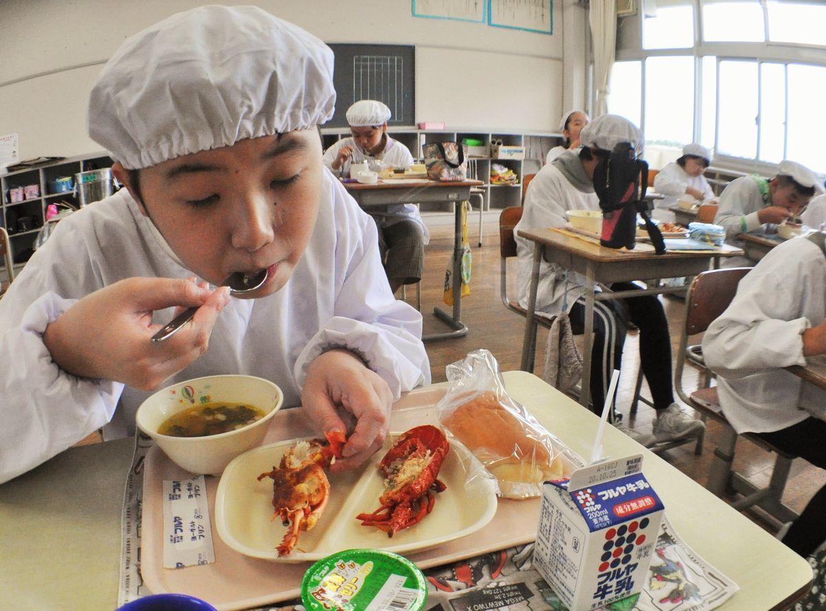 伊勢エビを食べる児童。余った二つ目をじゃんけんで勝ち取った=2020年10月19日、千葉県旭市鎌数の干潟小学校、高木潔撮影