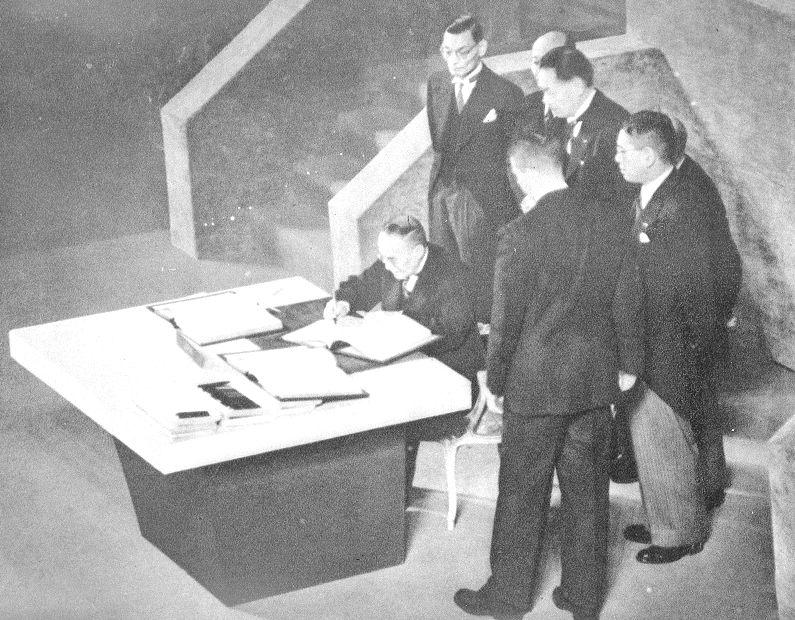 写真・図版 : 対日講和条約調印式で、講話条約書に署名する首席全権の吉田茂首相ら=1951年9月8日、サンフランシスコ