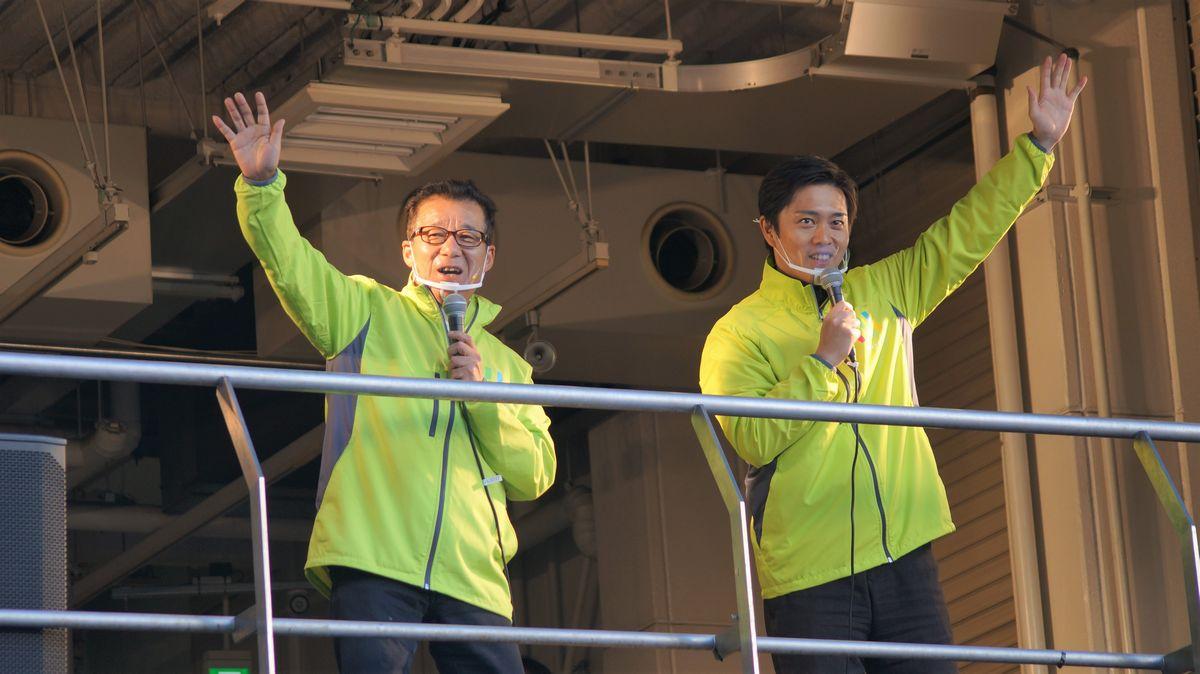 写真・図版 : 大阪ミナミのアメリカ村で、賛成への投票を市民に呼び掛ける松井一郎市長と吉村文洋知事。筆者撮影