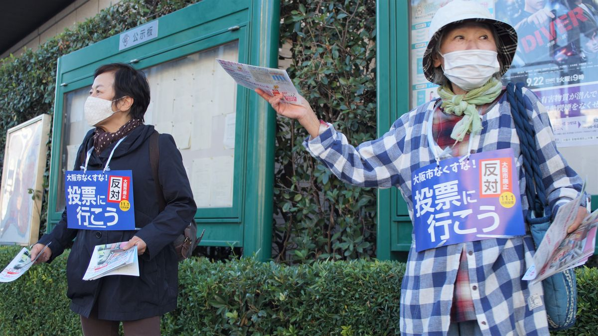写真・図版 : 大阪メトロ扇町駅の上でチラシを配る反対派の運動員。筆者撮影