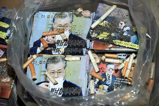 写真・図版 : ビラ合戦では北朝鮮も激しく応酬する。文在寅・韓国大統領を批判するビラが、ゴミ箱とみられる場所にタバコの吸い殻と一緒に捨てられた様子を北朝鮮の労働新聞が掲載した=2020年6月