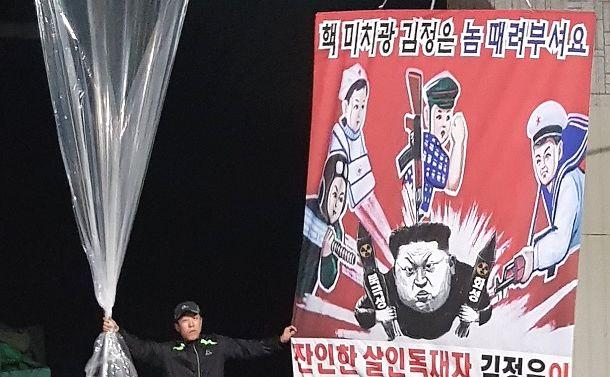 写真・図版 : 北朝鮮・金正恩氏をイラストで批判するビラをくくりつけた風船を飛ばす韓国の脱北者団体=韓国・坡州市