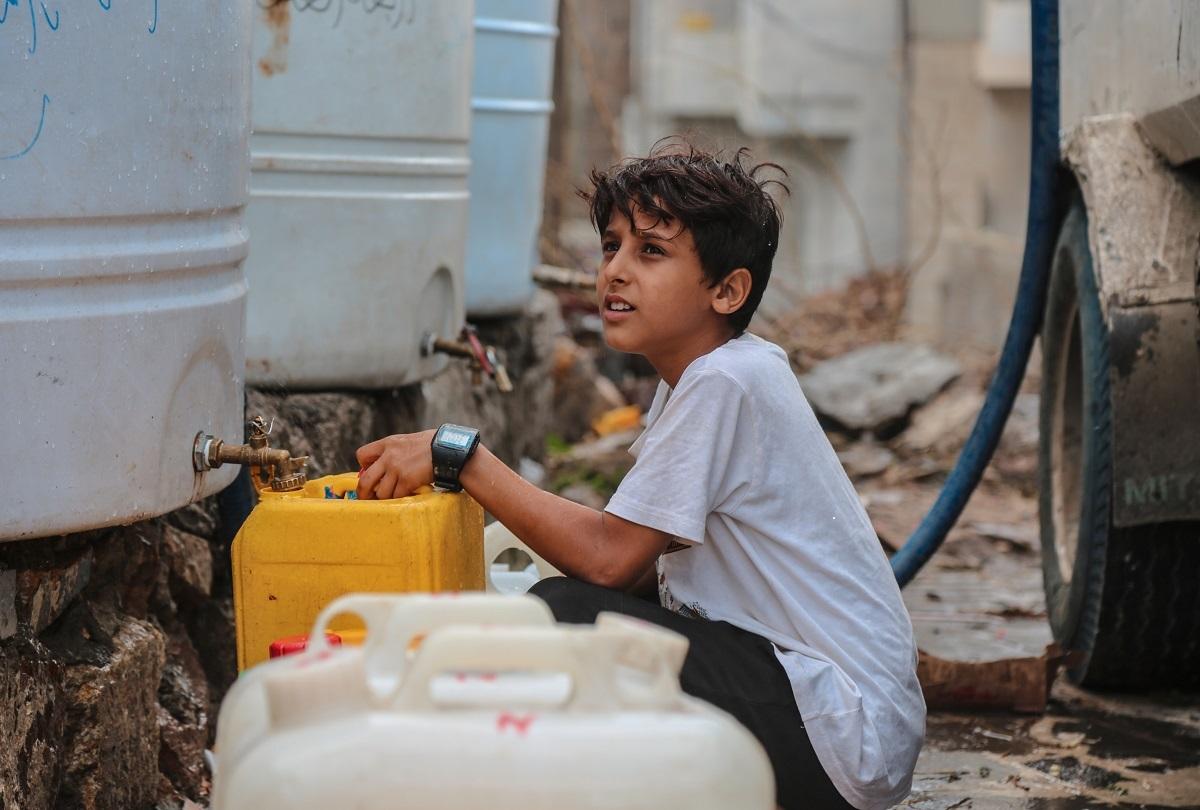 写真・図版 : 内戦による水不足で、給水をする少年=2020年7月、イエメン南西部の都市タイズで akramalrasny/Shutterstock.com