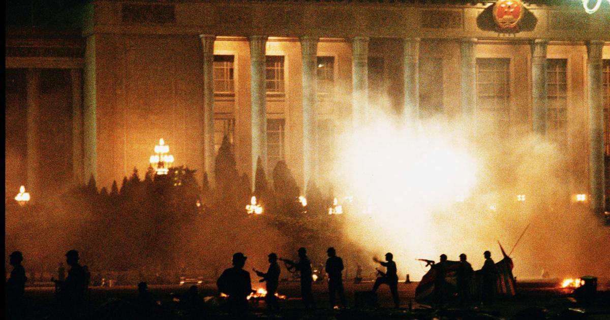 写真・図版 : 1989年6月3日未明、民主化を求めて北京の天安門広場で座り込みをしていた市民・学生に対し、戒厳軍が無差別銃撃を行った。6月4日午前5時ごろ、天安門広場を制圧したあとも、周辺に残る学生・市民に向かって発砲を続ける戒厳軍。後方の建物は人民大会堂=朝日新聞社