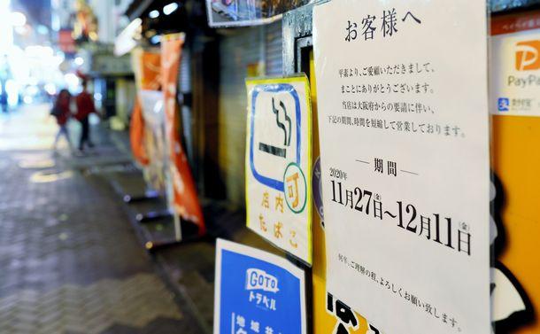 写真・図版 : 繁華街の飲食店に貼られた、時短営業のお知らせ=2020年11月27日、大阪市中央区道頓堀1丁目、矢木隆晴撮影