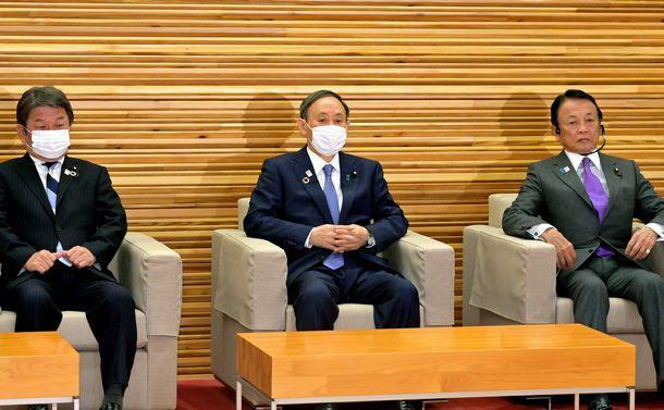 写真・図版 : 閣議に臨む菅義偉首相(中央)。左は茂木敏充外相、右は麻生太郎副総理兼財務相=2020年12月21日、首相官邸、恵原弘太郎撮影
