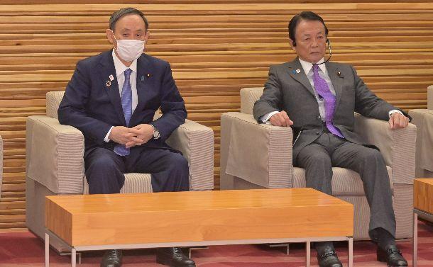 写真・図版 : 2021年度の当初予算案を決定した閣議に臨む菅義偉首相。右は麻生太郎副総理兼財務相=2020年12月21日、首相官邸